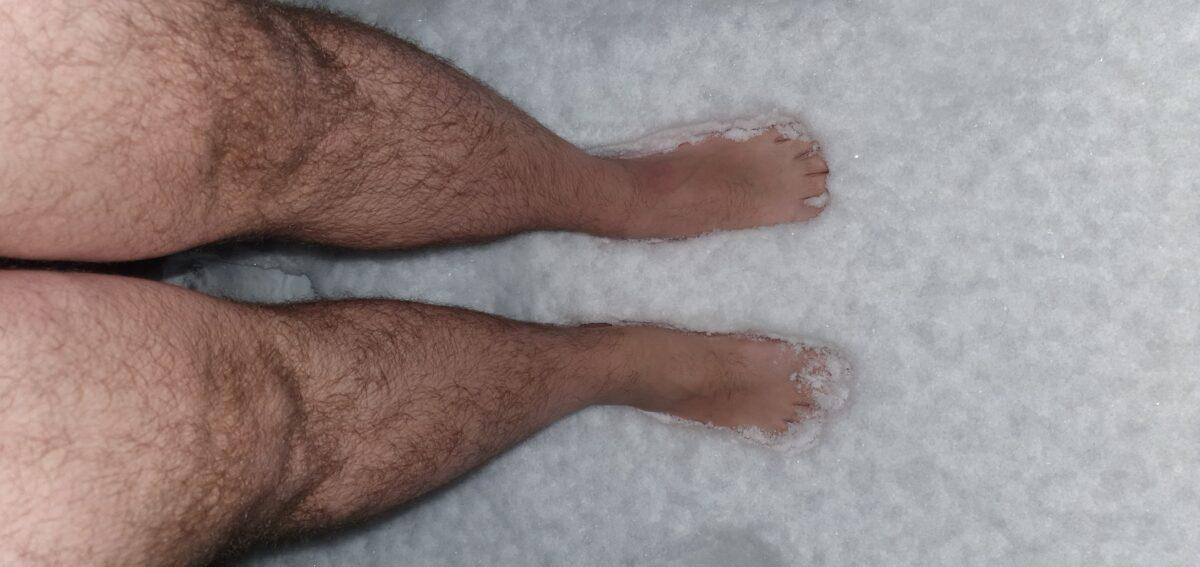 Ein paar nackte Füße stehen im Schnee