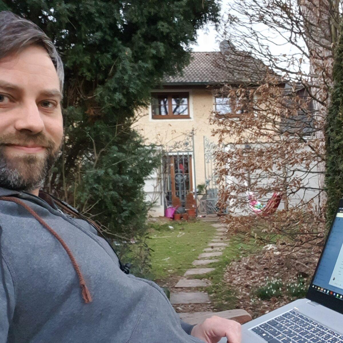 Stefan mit Laptop am Schoß im Garten