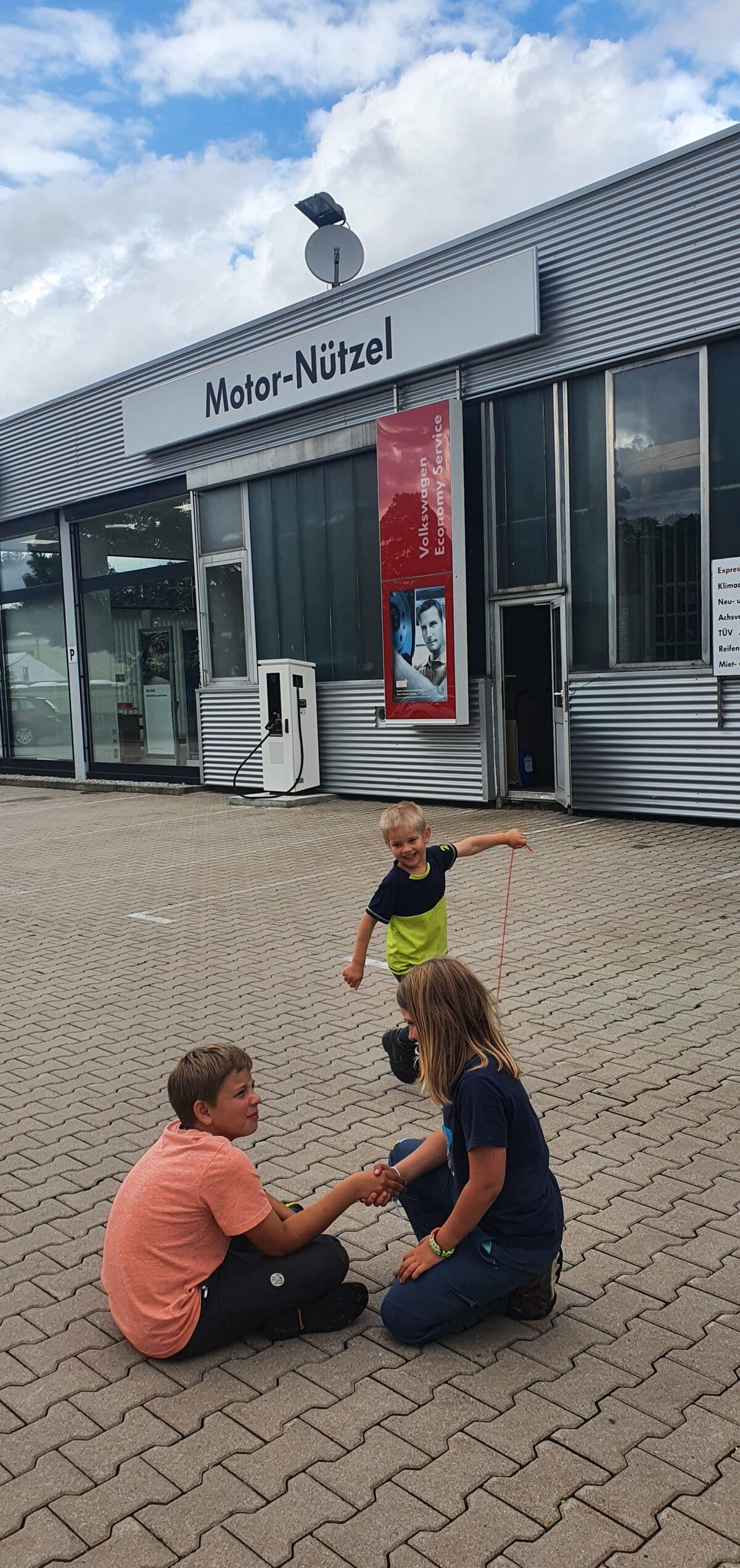 Drei Kinder spielen auf dem Hof einer Autowerkstatt